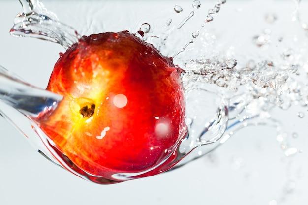Pomme rouge dans l'eau, éclaboussures