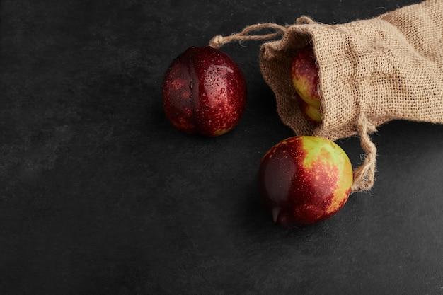 Pomme rouge dans un panier sur fond noir.
