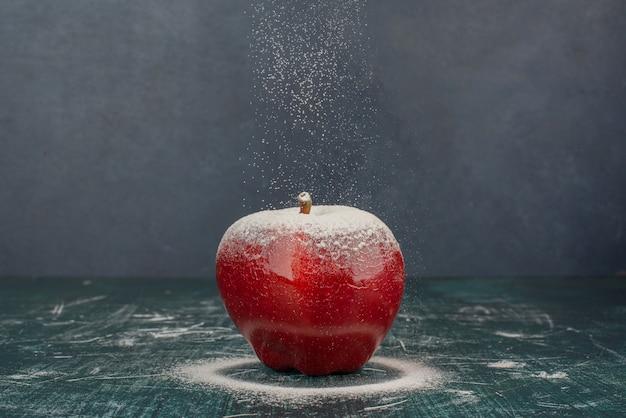 Pomme rouge décorée de poudre sur fond bleu.