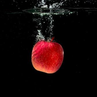 Pomme rouge entière éclaboussant dans l'eau sur fond noir