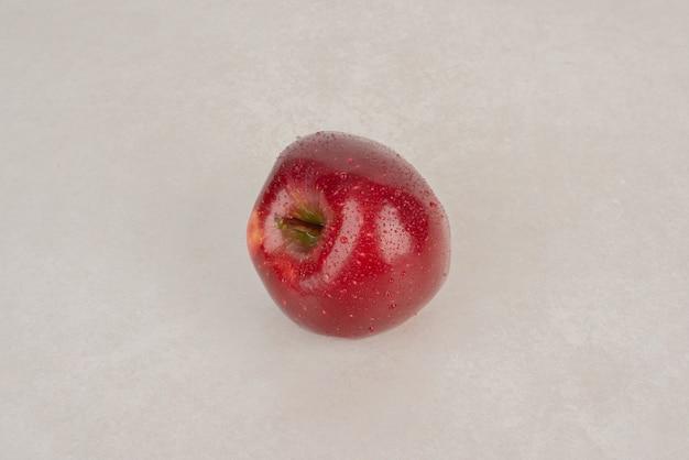 Une pomme rouge et fraîche sur fond blanc.