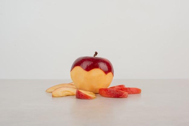 Pomme rouge hachée avec des tranches sur table blanche.