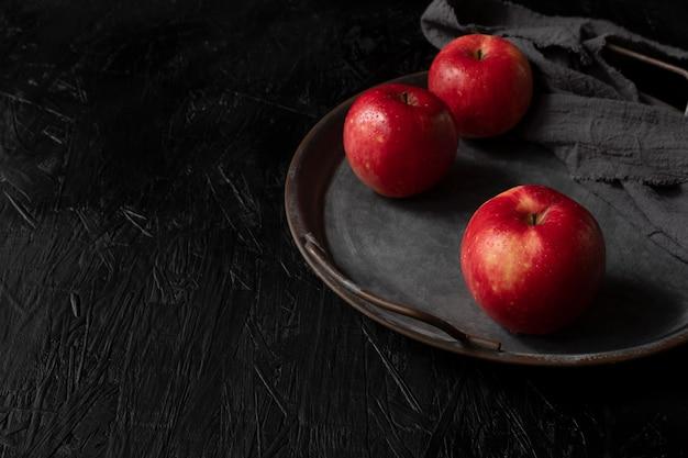 Pomme rouge isolée sur le fond en bois noir