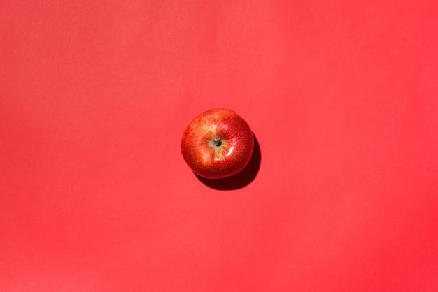 Pomme rouge isolée en studio avec fond rouge