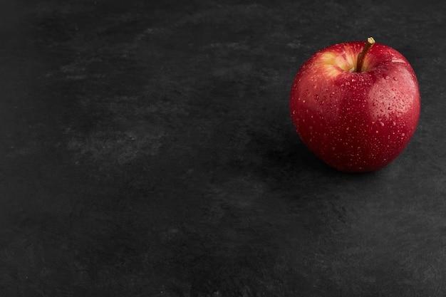 Une pomme rouge isolée sur une surface noire.