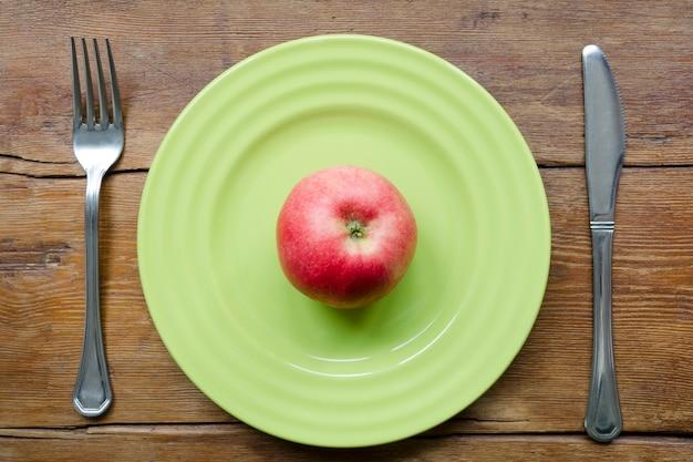 Pomme rouge juteuse sur la plaque verte avec fond de table en bois vintage
