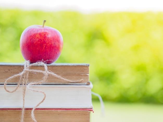 Pomme rouge mise en pile de vieux livres