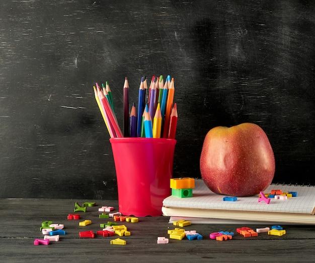 Pomme rouge mûre sur une pile de cahiers