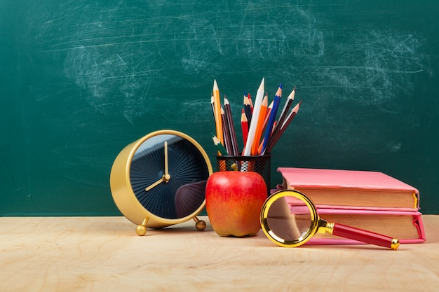 Pomme rouge sur une pile de livres, papier et crayon sur le bureau