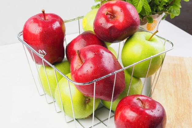 Pomme rouge et pomme verte dans le panier sur la table blanche