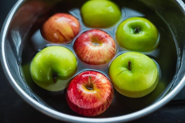 Pomme rouge et pomme verte nettoyant dans un bol