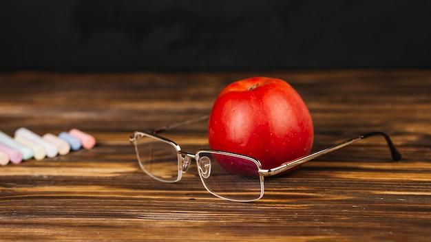 Pomme rouge près des lunettes