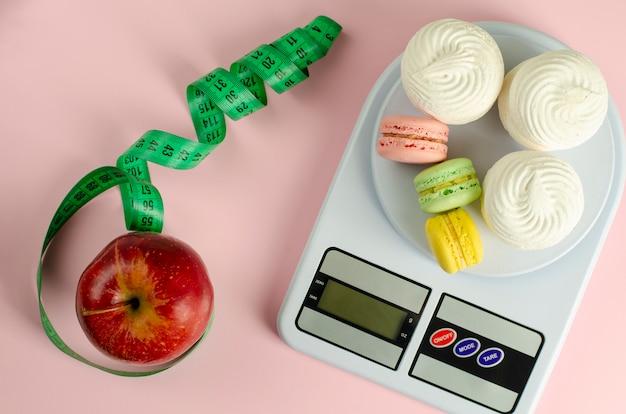Pomme rouge avec ruban à mesurer vert, balance de cuisine numérique avec macarons et meringues sur fond rose
