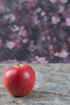 Pomme rouge songle isolée sur béton.