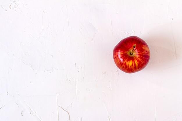 Pomme rouge sur tableau blanc.