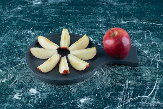 Pomme rouge tranchée et entière sur planche de bois sombre.
