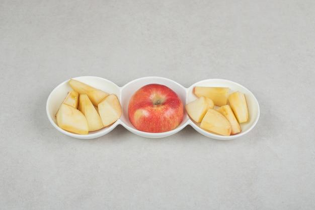Pomme rouge et tranches dans des bols blancs