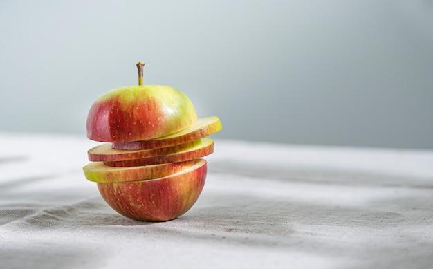 Pomme rouge verte juteuse coupée en tranches sur une nappe en lin naturel. vue de face et gros plan. orientation horizontale