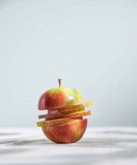 Pomme rouge verte juteuse coupée en tranches sur une nappe en lin naturel. vue de face et gros plan. orientation verticale