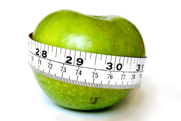 Pomme avec un ruban à mesurer autour d'elle.
