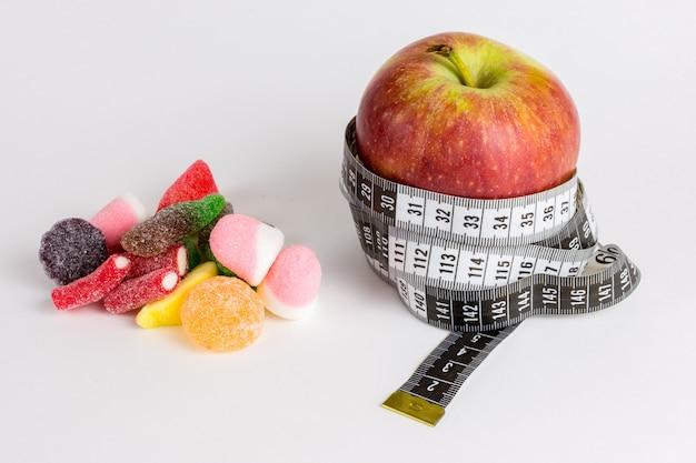 Pomme avec ruban à mesurer et bonbons haricots sur fond blanc