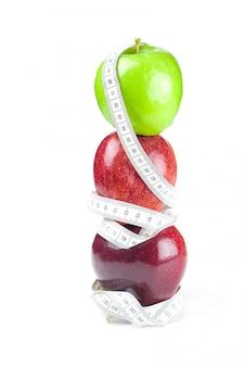 Pomme et ruban à mesurer isolé sur blanc