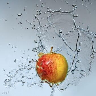 Pomme savoureuse avec un peu d'eau sur fond gris