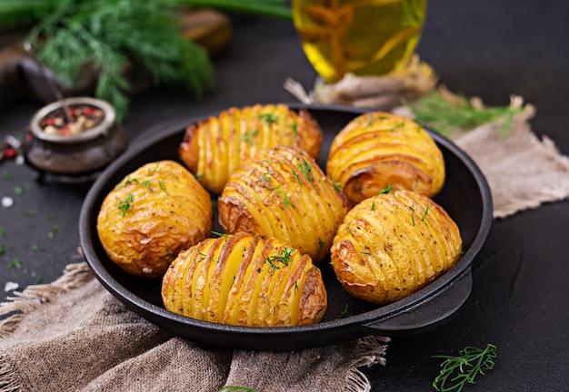 Pomme de terre au four avec des herbes sur fond noir. nourriture végétalienne. repas sain.
