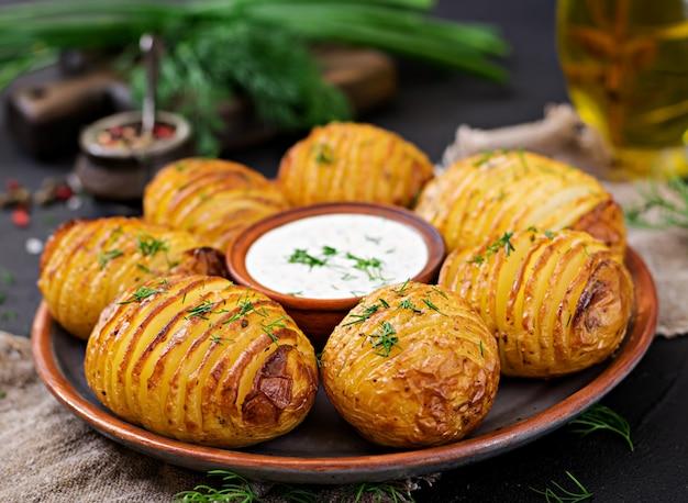 Pomme de terre au four avec des herbes et de la sauce sur fond noir. nourriture végétalienne. repas sain.