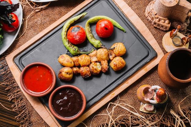 Pomme de terre au four sur planche de bois avec sauce tomate au poivre vue de dessus