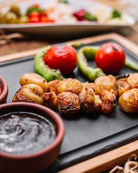 Pomme de terre au four sur planche de bois avec sauce tomate au poivre vue latérale
