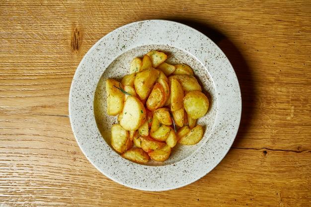 Pomme de terre au four (selyansky) avec sel, ail et oignons. cuisine ukrainienne traditionnelle en plaque blanche.