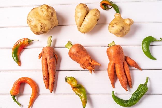 Pomme de terre, carotte et piment rouge sur bois blanc