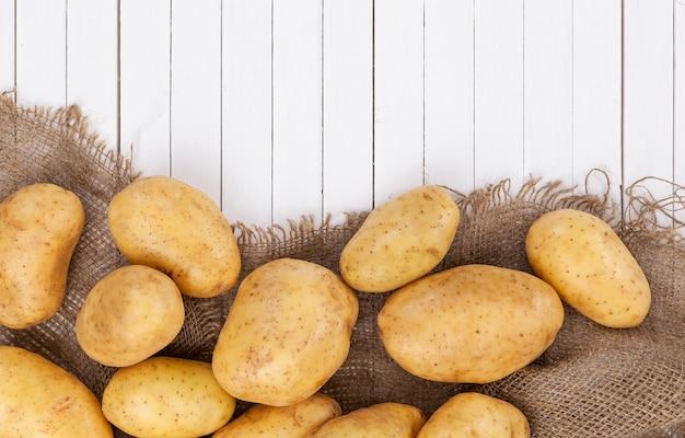 Pomme de terre crue, tas de pommes de terre sur toile de jute sur bois blanc