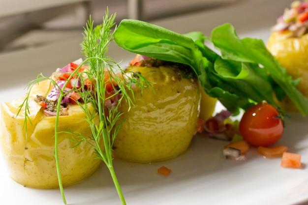 Pomme de terre farcie de riz et de légumes frais sur une assiette blanche