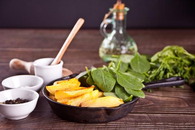 Pomme de terre frite aux herbes et épices sur la table en bois.