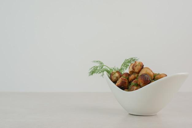Pomme de terre frite avec des verts sur plaque blanche.