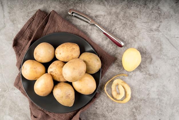 Pomme de terre pelée à côté d'un tas de pommes de terre crues