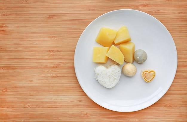 Pomme de terre et riz à la purée sur planche de bois.