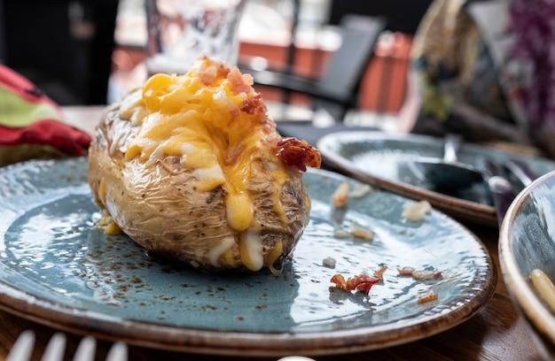 Pomme de terre rôtie sur une assiette bleue fourrée au cheddar et au bacon