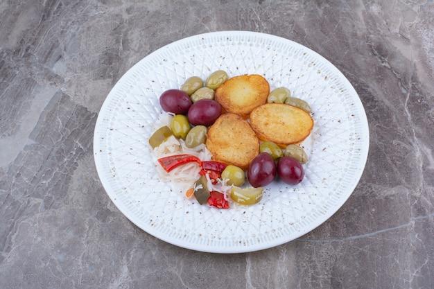 Pomme de terre rôtie et divers cornichons sur plaque blanche.