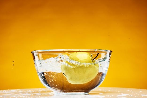 La pomme tombe dans un verre de fruit juteux dans de l'eau.