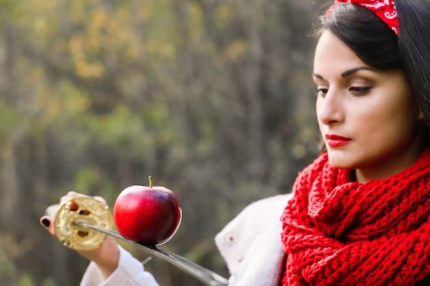 Une pomme sur le tranchant d'une épée entre les mains d'une jeune femme. épée japonaise.