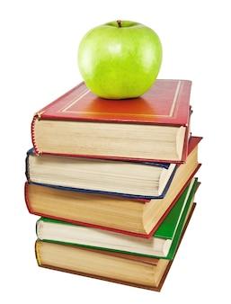 Une pomme verte au sommet d'une pile de vieux livres