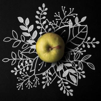 Pomme verte sur contour floral dessiné à la main