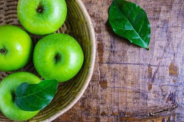 Pomme verte dans un panier sur une table en bois
