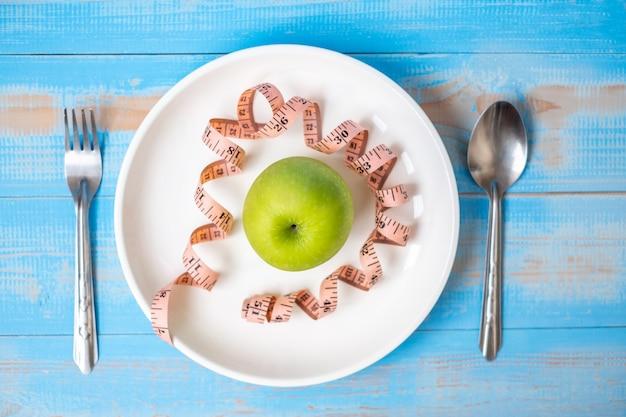 Pomme verte dans un plat blanc avec du ruban à mesurer rose sur une table en bois bleue