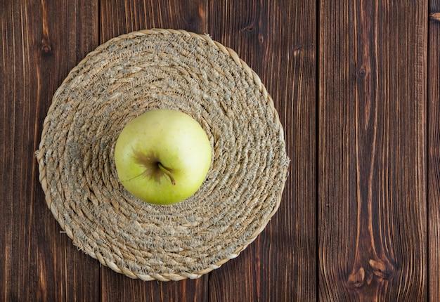 Pomme verte sur un dessous de plat et fond en bois. vue de dessus.