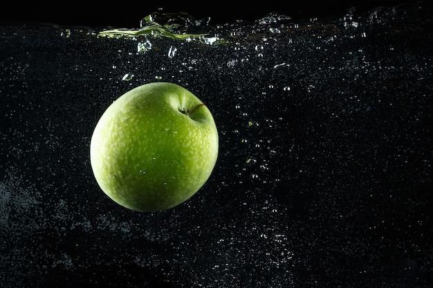 Pomme verte éclaboussant dans l'eau sur fond noir.