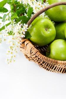 Pomme verte avec des fleurs dans un panier